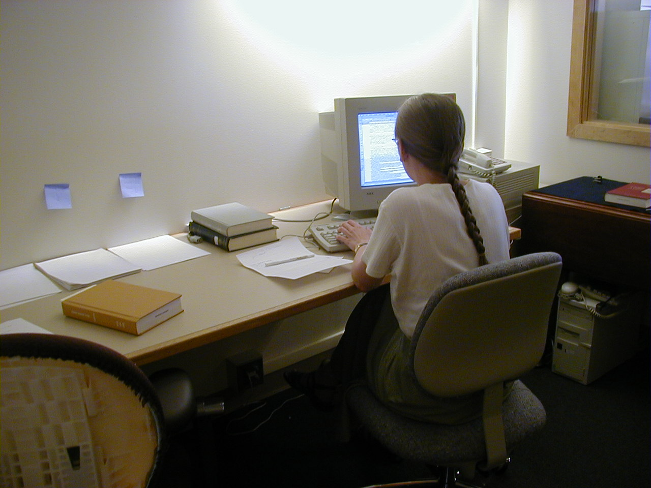 Photo of an editor working at a computer, writing notes for the final edition.